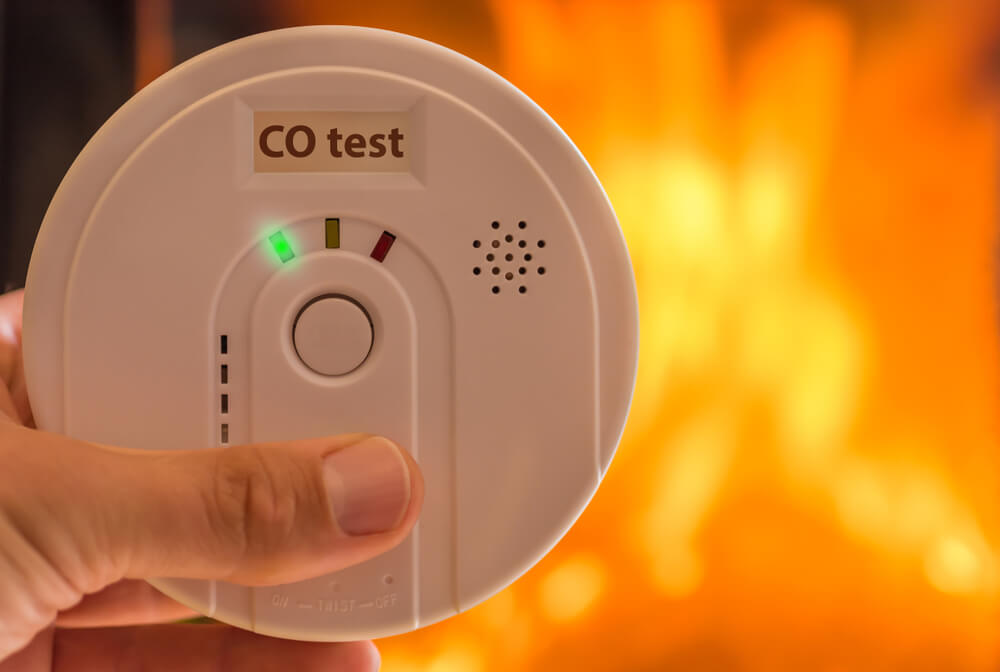 a hand holding a white carbon monoxide detector device.