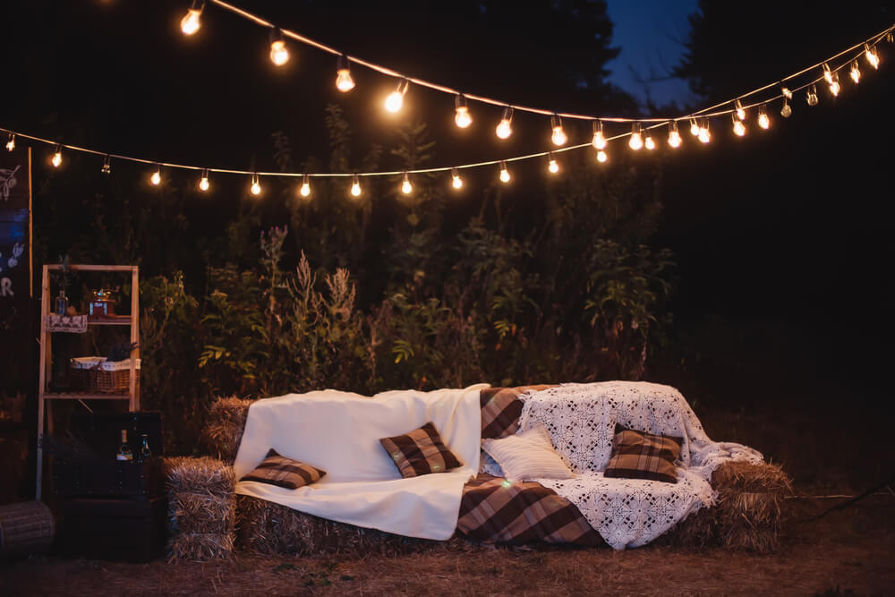 couch made of hay in the yard with light bulbs above it