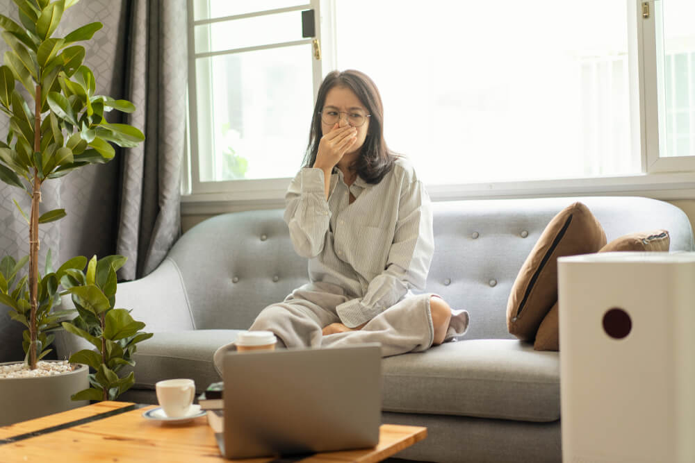 female Asian disgusted of indoor air quality in her house.