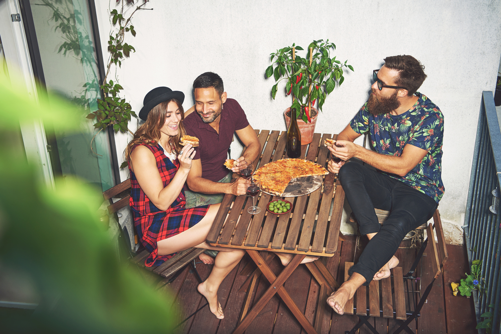 three people enjoying a pizza on a table