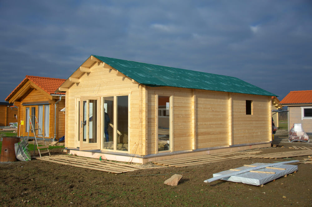 a wooden tiny dwelling with a sea green roofing. it's under construction. a man is inside the house.