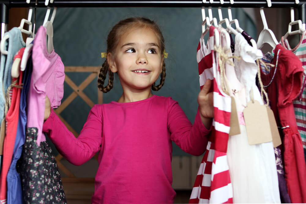 a little girl choosing dresses in a rack of clothes.