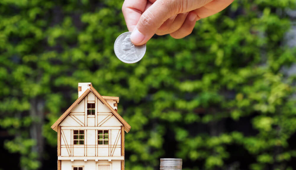 hidden costs of tiny home living - tiny house with coins beside it