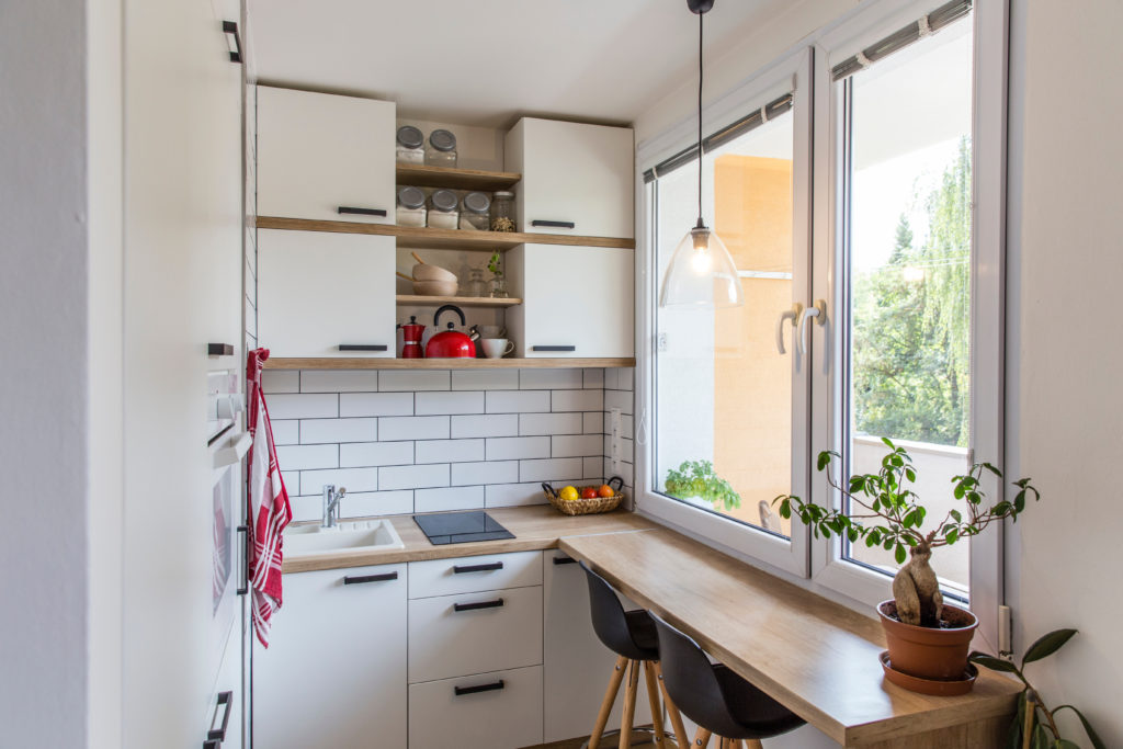 White tiny modern kitchen with red components, reconstruction, cosy small panel house