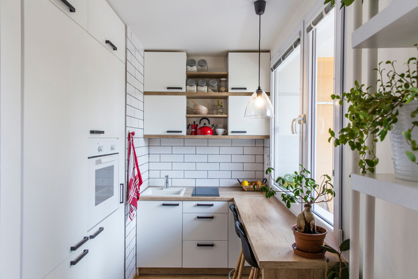 White kitchen with red components, cosy tiny home after the reconstruction in panel house