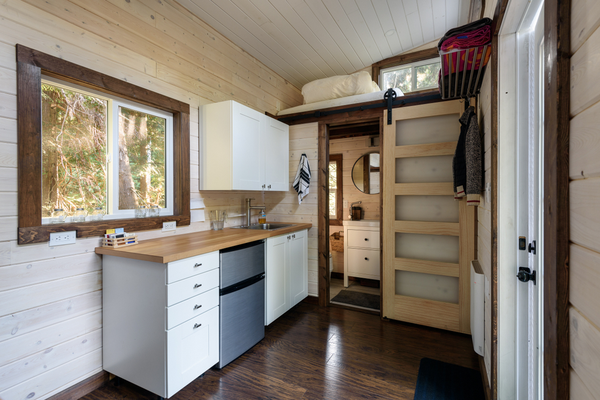 Interior design of a kitchen and bathroom in a tiny rustic log cabin.