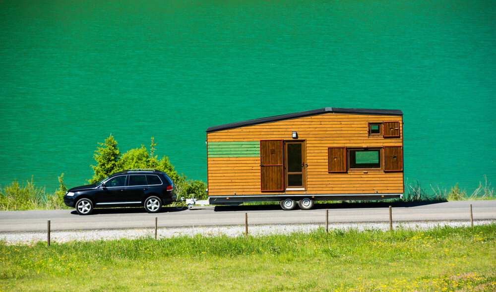 tiny home safety - tiny house on wheels with a lush green background