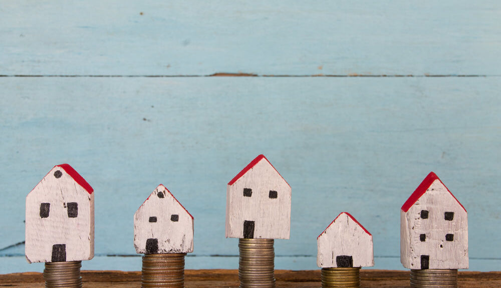 tiny houses and taxes - little houses on stack of coins