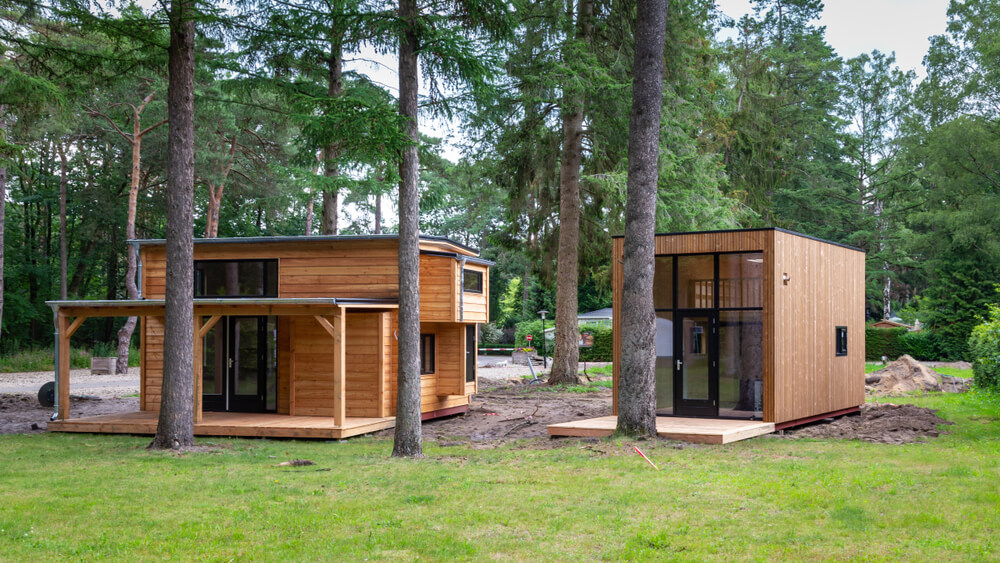 two brown tiny houses in a green, lush forest
