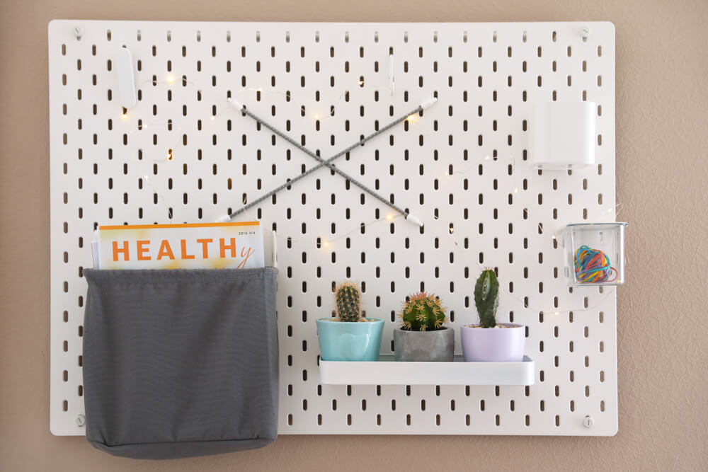 White pegboard with a pouch and cacti