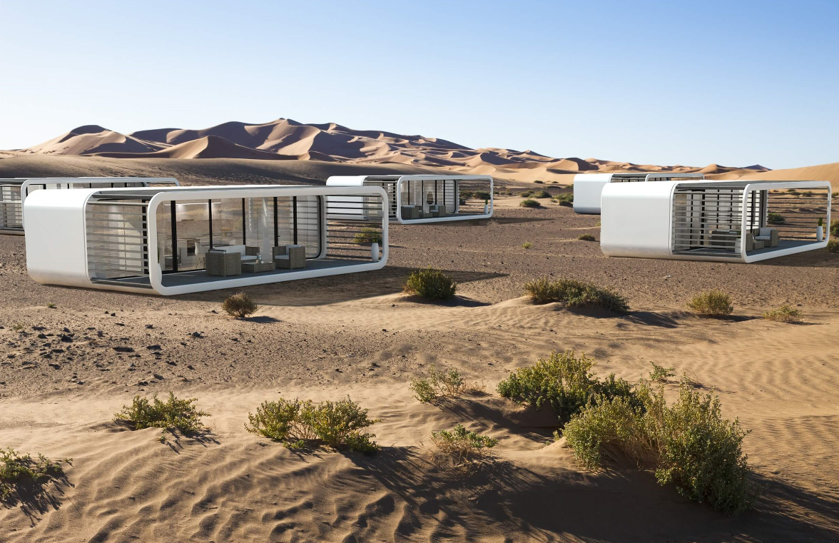 coodo white tiny houses on the desert. plenty of shrubs. afternoon sun.
