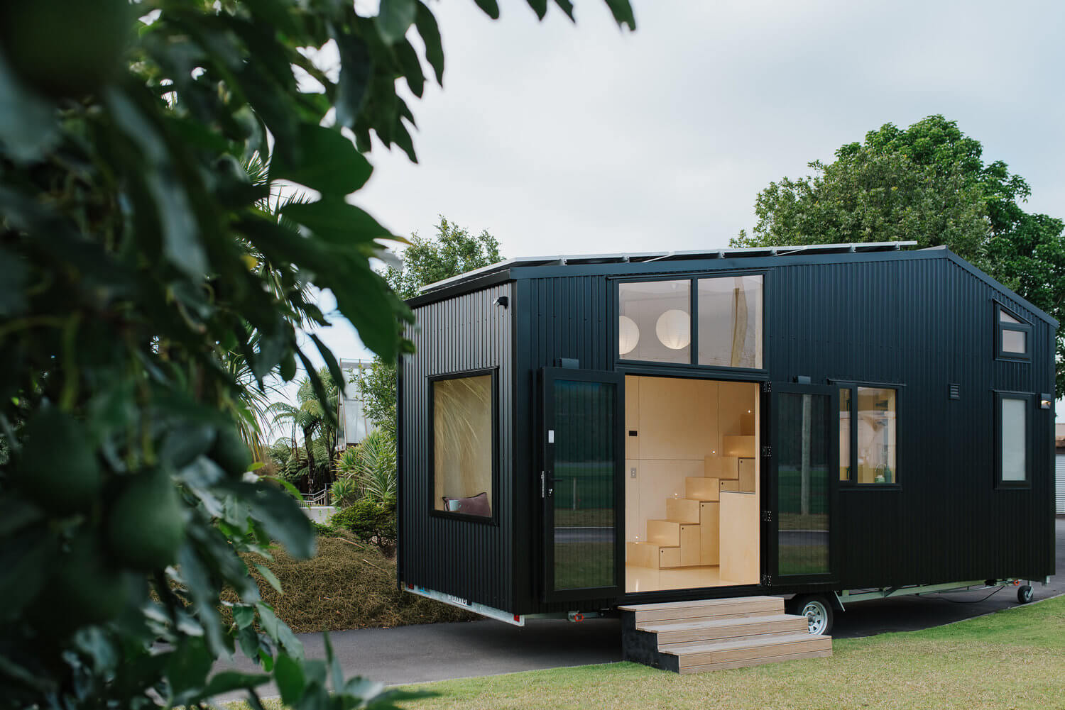 Front view of First Light Tiny House. Black tiny house on wheels. Greenery.