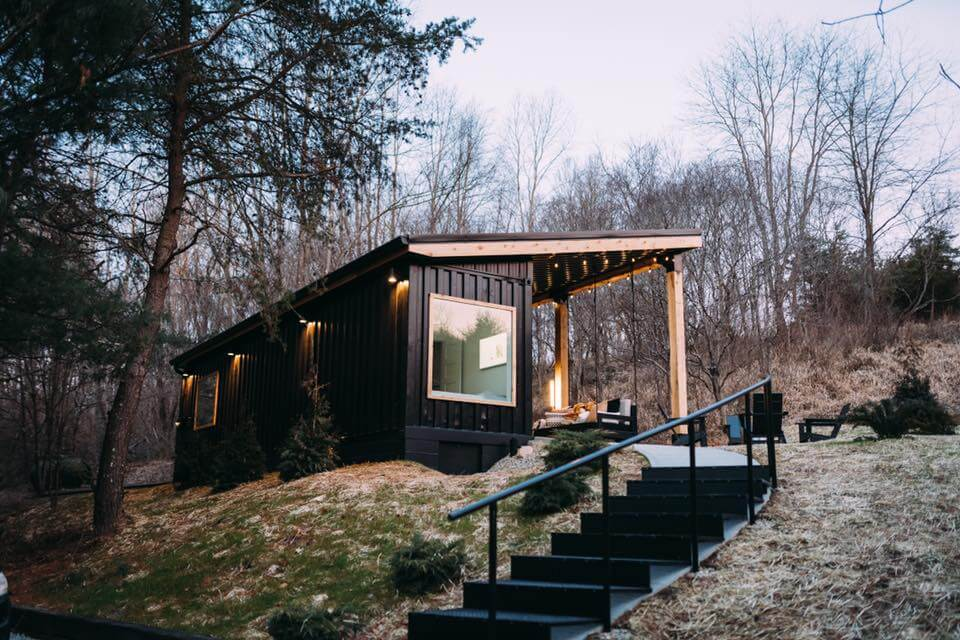 front view of The Lily Pad, black stairs leading to a black shipping container cabin.